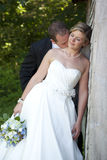 Newlywed bride and groom. Happy newlywed bride and groom with leafy green trees in background Royalty Free Stock Images