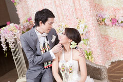 Newlywed bride and groom. Posing with Thai style garland and flower decoration in background Royalty Free Stock Images