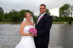 Newlywed bride and groom. Smiling by lake, countryside scene royalty free stock images