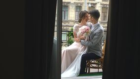 Newlywed bride and groom embracing on the balcony of old gothic cathedral. Young beautiful girl bride in a peignoir standing on the balcony overlooking the old stock video
