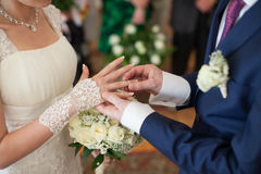 Newlywed bride and groom exchanging golden wedding rings at cere Stock Images