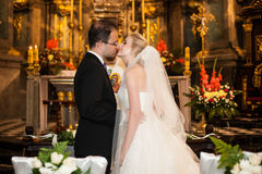 Newlywed bride and groom first kiss at wedding ceremony in churc Stock Photos