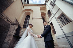 Newlywed bride and groom holding hands in old european street al Stock Images