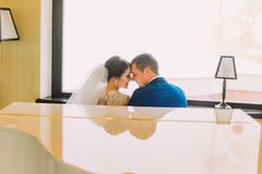 Newlywed bride and groom near the white grand piano going to kiss. Bright window on background Stock Photo