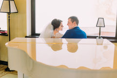 Newlywed bride and groom near the white piano going to kiss. Bright window on background Stock Images
