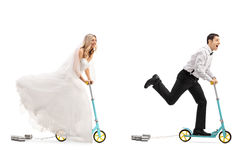 Newlywed bride and groom riding scooters. Full length portrait of a newlywed bride and groom riding scooters isolated on white background Royalty Free Stock Images