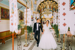 Newlywed bride and groom walking out of church holding hands.  Royalty Free Stock Photography