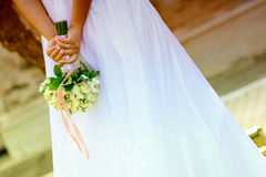 Newlywed bride holding bouquet. Newlywed bride holding a white rose bouquet behind her back outdoors Royalty Free Stock Photography