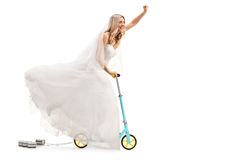 Newlywed bride riding a scooter and gesturing with her hand Stock Photos