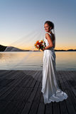 Newlywed bride at sunset with veil extended Stock Photo