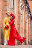 Newlywed couple in  ao-dai dresses Stock Photography