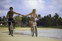 Newlywed couple at beach on bikes Stock Photography