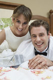 Newlywed Couple In Bed. Portrait of a happy newlywed couple with gift box in bed Royalty Free Stock Image