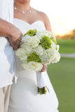 Newlywed couple with bouquet. Bodies of newlywed couple with bride in white dress holding bouquet of flowers Royalty Free Stock Images