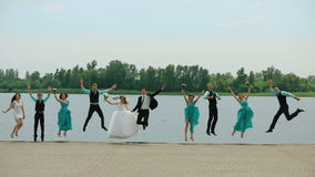 Newlywed couple with bridesmaids and groomsmen jumping at sunny beach stock video