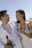 Newlywed Couple With Champagne Bottle And Flutes On Beach Stock Photo
