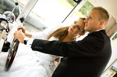 Newlywed couple driving Royalty Free Stock Photos