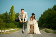 Newlywed couple driving scooter Royalty Free Stock Images
