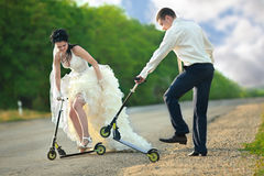 Newlywed couple driving scooter Royalty Free Stock Photos