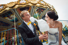 Newlywed couple at fairground. Eating candyfloss with carousel ride in background Stock Photos