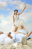 Newlywed couple fighting with pillows Stock Images