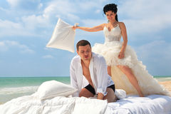 Newlywed couple fighting with pillows Stock Photos