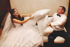 Newlywed couple fighting with pillows Stock Photography
