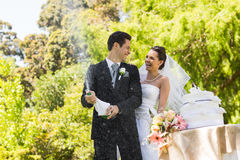 Newlywed couple with groom opening champagne bottle at park Royalty Free Stock Image