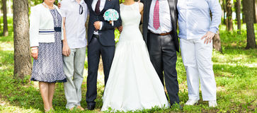 Newlywed couple  with guests  in green sunny park Stock Images