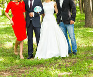 Newlywed couple  with guests  in green sunny park Royalty Free Stock Photos