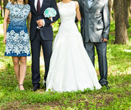 Newlywed couple  with guests  in green sunny park Royalty Free Stock Photo
