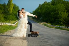 Newlywed couple hitchhiking on a road Royalty Free Stock Images