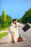 Newlywed couple hitchhiking on a road Royalty Free Stock Photos