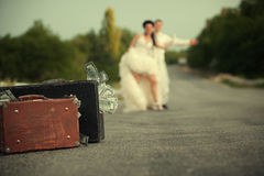 Newlywed couple hitchhiking on a road Stock Image