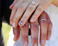 Newlywed couple holding hands. Hands of newlywed couple showing wedding rings Royalty Free Stock Photography