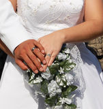 Newlywed couple holding hands. Wedding rings on hands of newlywed couple with flower bouquet Stock Photo
