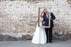 Newlywed couple holding portrait frame, brick wall Stock Photo