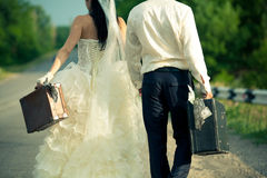 Newlywed couple holding  suitcases of cash Stock Photo