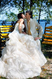 Newlywed couple kissing. Closeup of newlywed couple kissing on park bench with lake in background Royalty Free Stock Photo