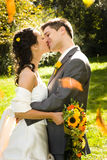 Newlywed couple kissing. Half body portrait of young newlywed couple kissing outdoors, bride with bouquet Royalty Free Stock Photography