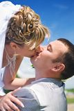 Newlywed couple kissing. Side portrait of newlywed young couple kissing outdoors with blue sky background Royalty Free Stock Photography