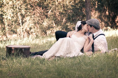 Newlywed couple kissing. Newlywed young couple kissing on field in countryside; groom in rustic clothing Royalty Free Stock Photos