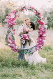 The newlywed couple is kissing behind the wedding peonies arch in the sunny wood. Close-up portrait. The newlywed couple is kissing behind the wedding peonies Royalty Free Stock Photos