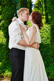 Newlywed couple kiss. Groom bride wedding day love. Newlywed couple hugging and kissing each other lovingly. Wedding day love kiss Stock Photo