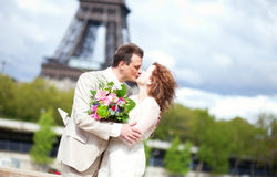 Newlywed couple kissing near the Eiffel tower Royalty Free Stock Images