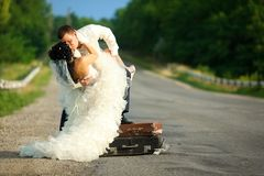 Newlywed couple kissing on a road Royalty Free Stock Photography