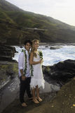 Newlywed couple on lava cliffs Stock Photography
