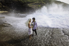 Newlywed couple on lava cliffs Stock Photo