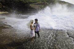 Newlywed couple on lava cliffs Stock Photo