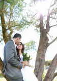 Newlywed couple lean back on tree in sunny day Stock Photos